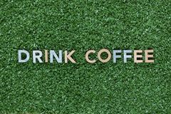 The words Drink coffee made from multicolored letters on grass background, shot from above, aligned in the center stock photography