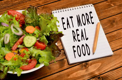 The words Eat more real food. On notebook royalty free stock images
