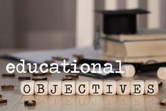 Words  EDUCATIONAL OBJECTIVES composed of wooden dices. Word EDUCATIONAL OBJECTIVES composed of wooden dices. Black graduate hat and books in the background royalty free stock images
