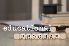 Words  EDUCATIONAL PROGRAM composed of wooden dices. Black graduate hat and books in the background. Closeup stock photo