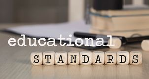 Words  EDUCATIONAL STANDARDS composed of wooden dices. Black graduate hat and books in the background. Closeup royalty free stock images