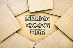 Words Enjoy Every Day make by black alphabet stamps on cardboard. With some piece of cardboard Royalty Free Stock Photography