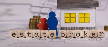 Words ESTATE BROKER composed of wooden letter. Small paper house in the background. Closeup royalty free stock photos