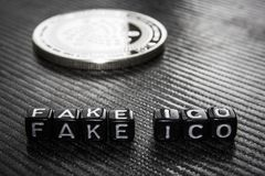 Words fake ico of black cubes and silver coin dark . stock photos