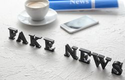 Words FAKE NEWS made of letters on textured table stock photography