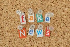 Words Fake News written with cut out magazine letters on bulleti royalty free stock photos