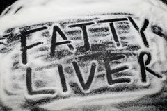 Words Fatty Liver written with and in sugar grains, sugar is know to cause fatty liver disease. Words Fatty Liver written with and in sugar grains, sugar is royalty free stock photos