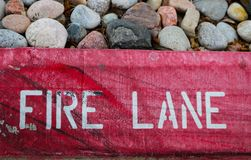 Fire Lane stenciled on a scuffed and chipped red painted curb with rocks from flower bed on top. The words Fire Lane stenciled on a scuffed and chipped red Stock Photography
