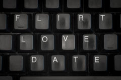 The words flirt, love, date on a black keyboard. Words date, love, flirt on a black computer keyboard stock image