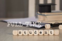 Words FULL-TIME STUDENT composed of wooden dices. Black graduate hat and books in the background. Closeup royalty free stock photography