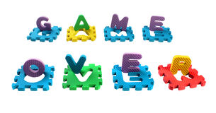Words Game Over composed of cut out letters of toy plastic alphabet puzzle, isolated on white background Royalty Free Stock Image