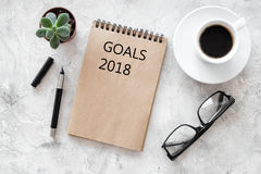 Words Goals for 2018 writting in notebook near glasses and cup of coffee on grey stone background top view mockup