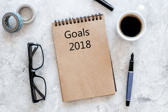 Words Goals for 2018 writting in notebook near glasses and cup of coffee on grey stone background top view mockup stock image
