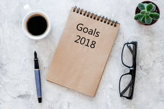 Words Goals for 2018 writting in notebook near glasses and cup of coffee on grey stone background top view mockup Stock Images