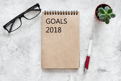 Words Goals for 2018 writting in notebook near glasses on grey stone background top view mockup royalty free stock photos