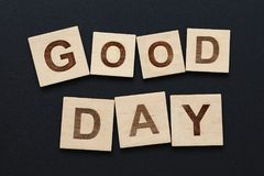 Words GOOD DAY on wooden signs over black. Close up two words GOOD DAY on wooden scrabble letter signs over black board background stock photography
