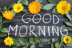 Words Good Morning with Leaves and Marigold Flowers. On a Rustic Wooden Background royalty free stock photos