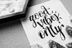 Good Vibes Only Black and White. The words `good vibes only` in calligraphy surrounded by rocks and sand royalty free stock photo