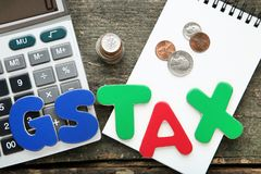 Words GST and Tax with coins stock photo