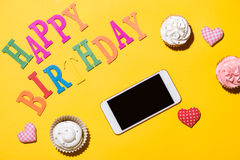 Words Happy Birthday with cupcake and smartphone on yellow backg Royalty Free Stock Image