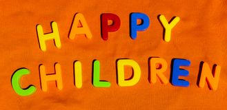 The words Happy Children written by toy letters. The words composed from colorful children toy big letters of alphabet on the bright background. The words Happy stock photography