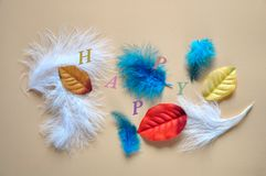 The Words Happy on Colorful Feathers and Leaves Background. The words Happy on colorful feathers and leaves on pastel background stock images