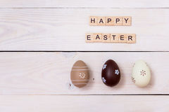 The words of Happy Easter are written on wooden cubes and eggs. Happy Easter concept on white wooden background Stock Image