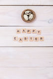The words of Happy Easter are written on wooden cubes and eggs. Happy Easter concept on white wooden background Royalty Free Stock Image