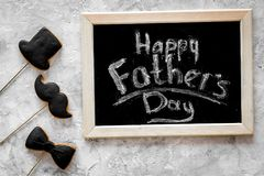 Words happy Father`s day written on blackboard. Black tie, mustache and hat cookies. Grey stone background top view royalty free stock photography