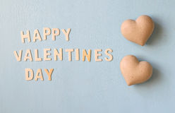 The words happy valentines day made with block wooden letters next to couple of hearts on light blue wooden background Stock Photos