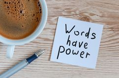 Words have power concept. Motivating and inspiring note at wooden table with morning coffee cup