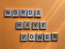 Words Have Power, isolated on orange background. The words  Words Have Power written in 3d wooden alphabet letters isolated on an orange background with copy stock photo