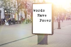 Words have power - words, phrase. On a white background billboard in the center of the city against sun rays royalty free stock photo