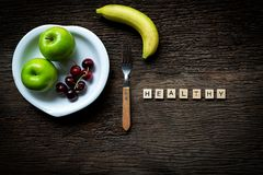 Words of Healthy concepts collected in crossword with wooden cubes. Green apple and cherry background, Royalty Free Stock Image