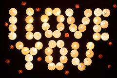 Words I LOVE YOU formed by glowing candles and decorated with flowers. Greeting to St. Valentine`s Day royalty free stock photography
