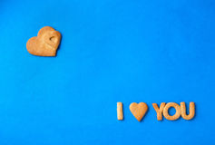 Words - I love you. Words I love you made of cookies placed on a blue paper surface with a heart on the top left corner Stock Photography