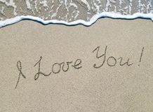 Words I love you outline on sand with wave brilliance. Words `I love you` outline on wet sand with wave brilliance royalty free stock photos