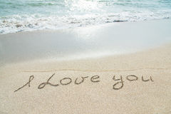 Words I love you outline on the wet sand. With the wave brilliance Stock Photo