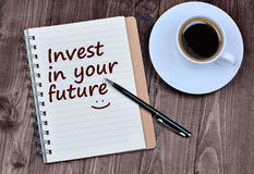 The words Invest in your future on notebook. Page Royalty Free Stock Photos