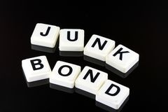 The Words Junk Bond - A Term Used For Business in Finance and Stock Market Trading. The Words Junk Bond Spelled Out With White Tiles On Black Background Stock Photo