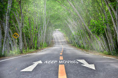Words of keep moving with white arrow on road Stock Images