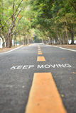 Words of keep moving with yellow line marking on road Stock Images