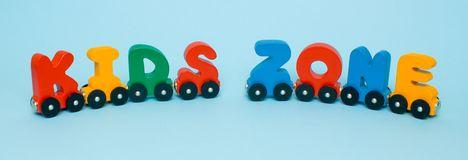 Words kids zone made of letters train alphabet. Bright colors of red yellow green and blue on a white background. Early childhood. Development, learning to read royalty free stock image