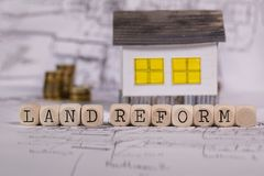 Words LAND REFORM composed of wooden letter. Small paper house in the background. Closeup stock photography