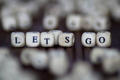The words let`s go in old wood type - wooden cubes. The words lets go in old wood type Royalty Free Stock Photography