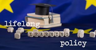 Words LIFELONG  LEARNING POLICY composed of wooden letters. Black graduate hat on EU flag in the background. Closeup royalty free stock photos