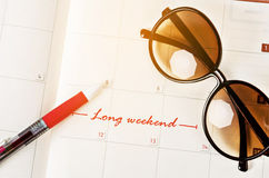 The words Long Weekend on calendar. The words Long Weekend written on a calendar page to remind Stock Photography