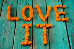 Words Love It written by fresh bright orange pumpkin cubes on wo Stock Images