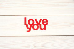 Words love you carved out of red paper. On a wooden background Royalty Free Stock Images