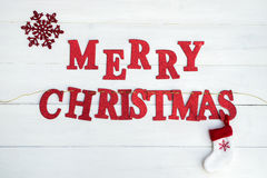 Words Merry Christmas. Made from Red Glittering Letters Placed on the String and Large Snowflakes are laying on White Wooden Background Stock Image